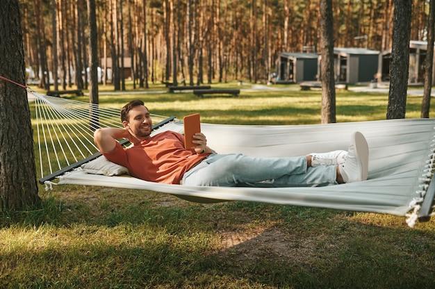 Hombre atractivo mirando tableta relajándose en una hamaca