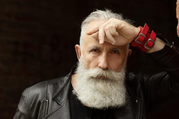 Hombre atractivo modelo senior barbudo en contexto urbano.