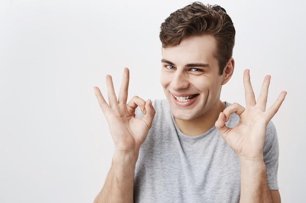 Hombre atractivo con ojos azules, sonriendo con alegría mostrando signo bien con ambas manos, contento después de reunirse con su novia aislada. expresiones faciales humanas y emociones