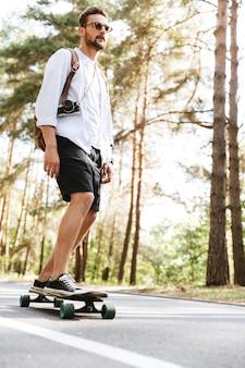 Hombre atractivo en patineta al aire libre