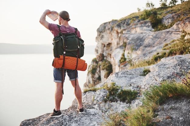 Hombre atractivo que disfruta de la vista del paisaje de las montañas sobre la superficie del agua. concepto de vacaciones de aventura de estilo de vida de viaje
