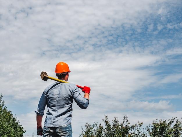Hombre atractivo que sostiene un martillo en el parque