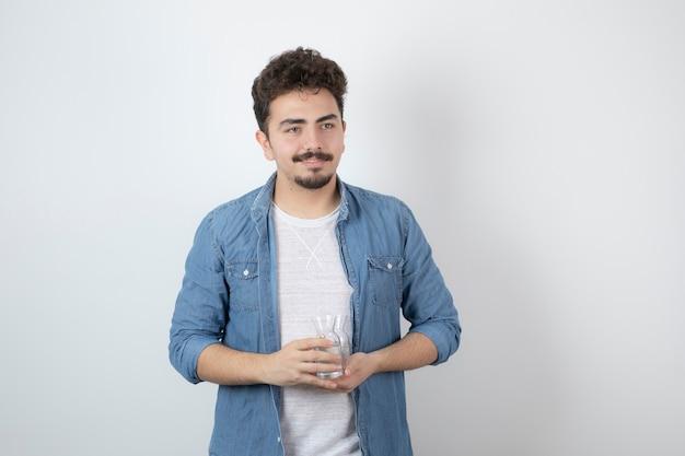 Un hombre atractivo sonriente de pie y sosteniendo un frasco de vidrio.