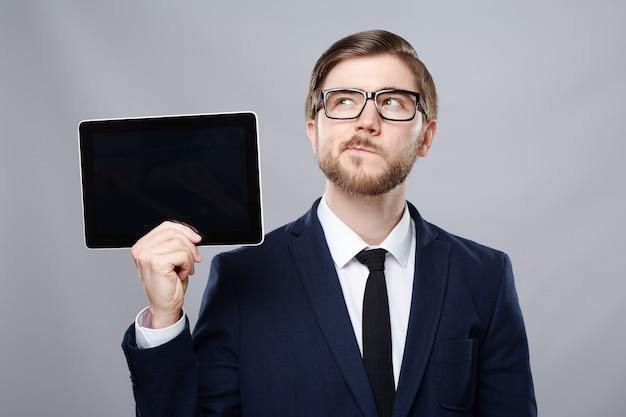 Hombre atractivo vestido con traje y gafas de pared sosteniendo una tableta y pensando, concepto de negocio, espacio de copia, retrato, maqueta.