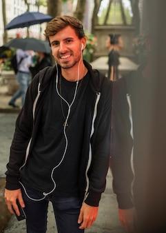 Hombre con auriculares apoyado contra una pared.