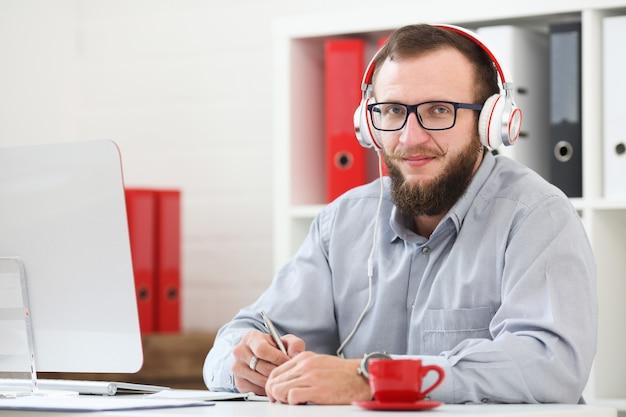 Un hombre con auriculares escucha música y aprende en línea. toma notas en un cuaderno y mira a la cámara.