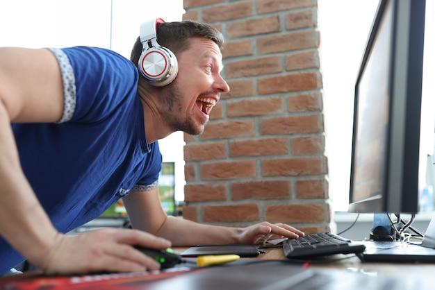 Hombre en auriculares gritando al monitor de la computadora