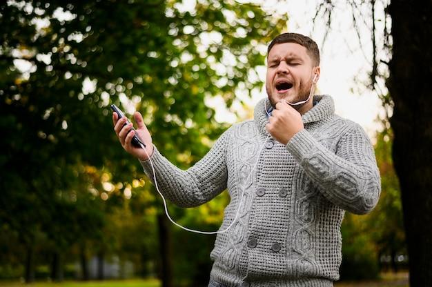 Hombre con auriculares en los oídos cantando en el parque