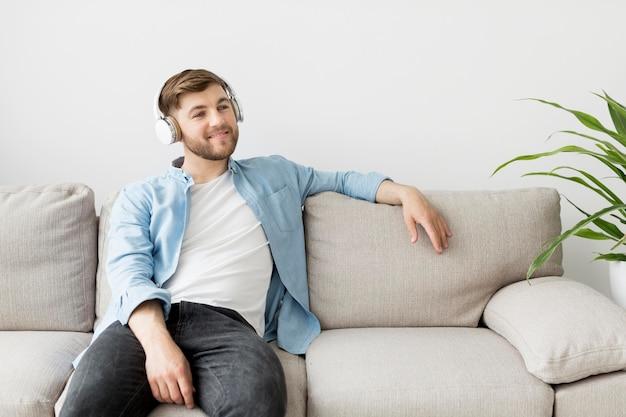 Hombre con auriculares en el sofá