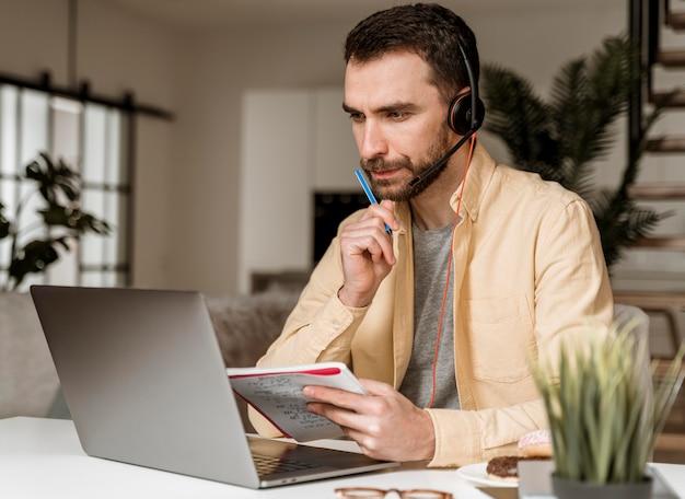 Hombre con auriculares con videollamada en portátil