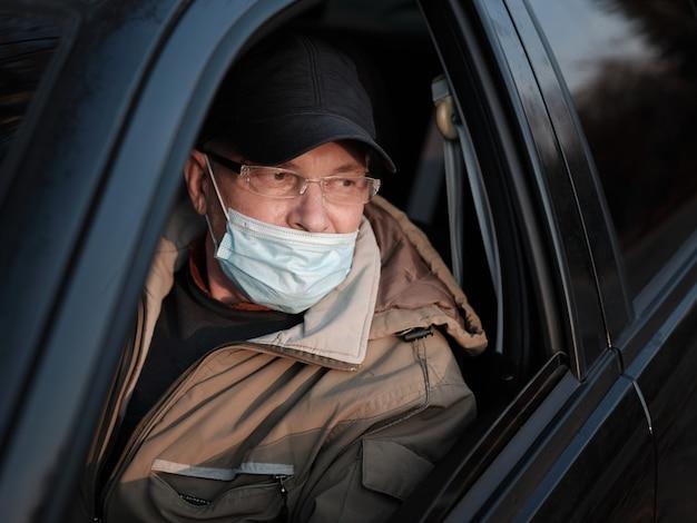 Un hombre en un automóvil con una máscara médica usada incorrectamente