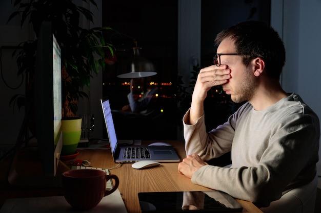 Hombre autónomo cansado frotándose los ojos, sentado frente a la computadora de escritorio / portátil a altas horas de la noche, durante el período de autoaislamiento y trabajo remoto en casa, se queda dormido por fatiga.