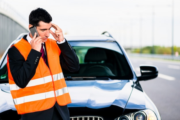 Hombre con avería de coche llamando a la empresa de remolque