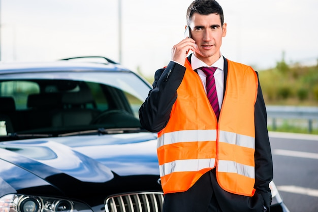 Hombre con avería del coche llamando a la empresa de remolque