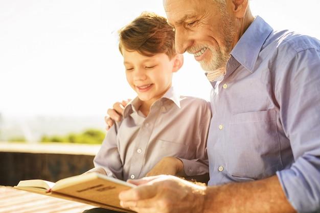 El hombre ayuda al nieto a estudiar. encuentro familiar en el parque.