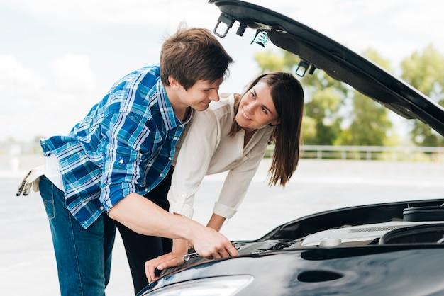 El hombre ayuda a la mujer a arreglar su auto