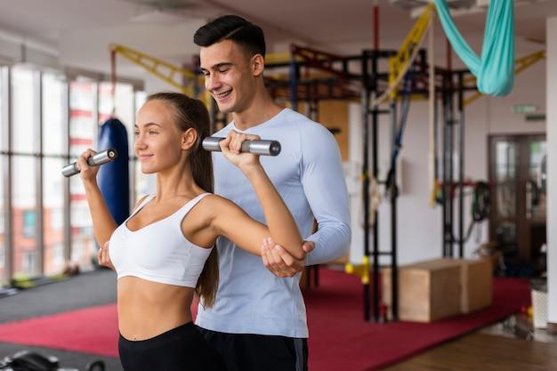 Hombre ayudando a la mujer con su ejercicio