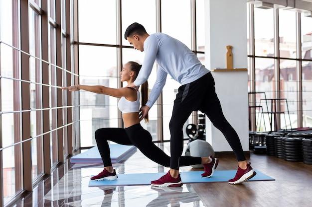 Hombre ayudando a mujer con su entrenamiento