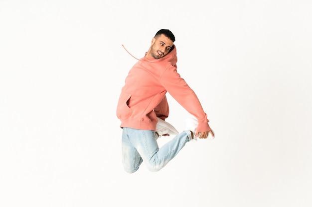 Hombre bailando estilo de baile callejero sobre pared blanca aislada