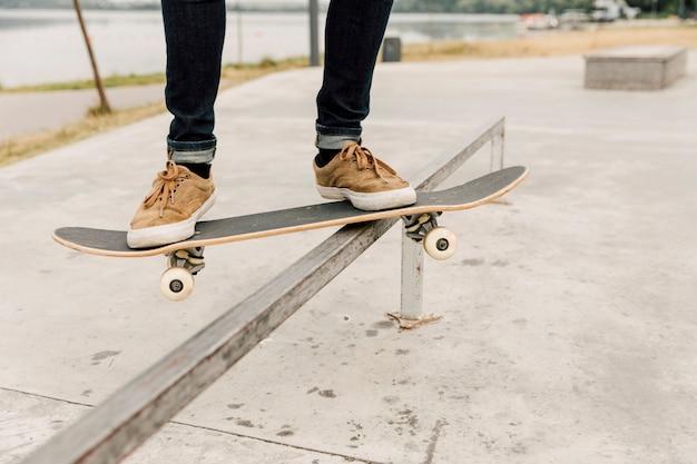 Hombre balanceando patineta en la barandilla