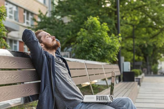 Hombre en banco de la ciudad con laptop