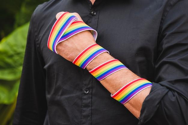 Hombre con banda en colores lgbt en mano.