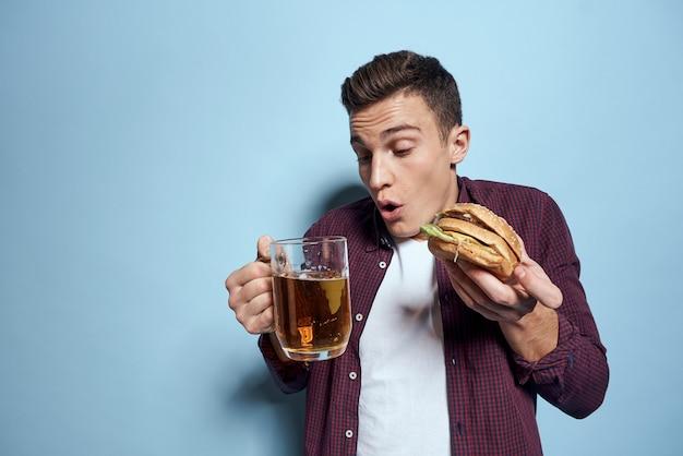 Hombre con una bandeja de comida chatarra: hamburguesas y papas fritas, cerveza