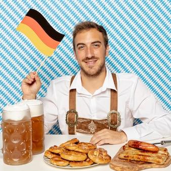 Hombre con bandera alemana, comida y cerveza