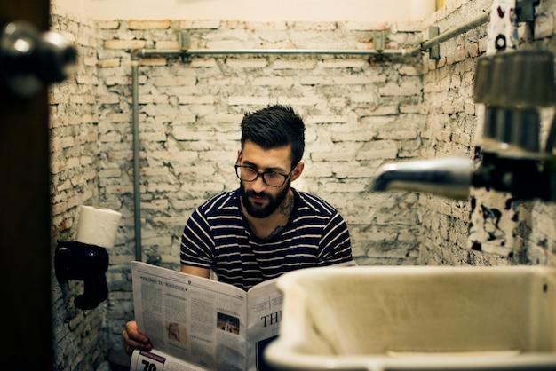 Hombre en un baño leyendo un periódico