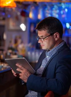 Hombre en el bar mirando la tableta digital