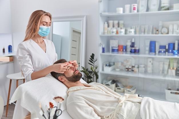 El hombre con barba está acostado boca arriba, recibiendo un masaje de estiramiento facial. tratamiento de belleza de masaje facial. concepto de bienestar, belleza y relajación.