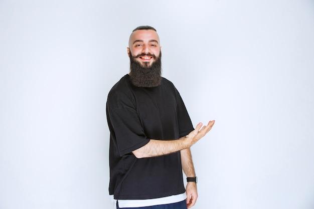 Hombre con barba apuntando a alguien alrededor.