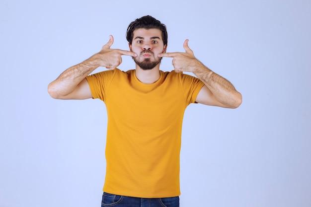 Hombre con barba apuntando a su boca