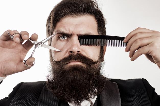 Hombre con barba y bigote y barba larga. peluquero en peluquería con tijeras