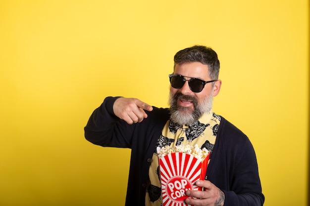 Hombre con barba blanca y gafas de sol sobre fondo amarillo aislado sosteniendo un gran cubo de palomitas de maíz mientras apunta hacia adelante