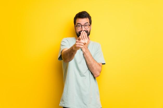 Hombre con barba y camisa verde apuntando con el dedo a alguien y riendo