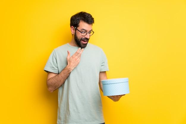 Hombre con barba y camisa verde con caja de regalo en las manos