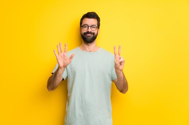 Hombre con barba y camisa verde contando siete con los dedos.