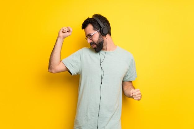 Hombre con barba y camisa verde escuchando música con auriculares y bailando.