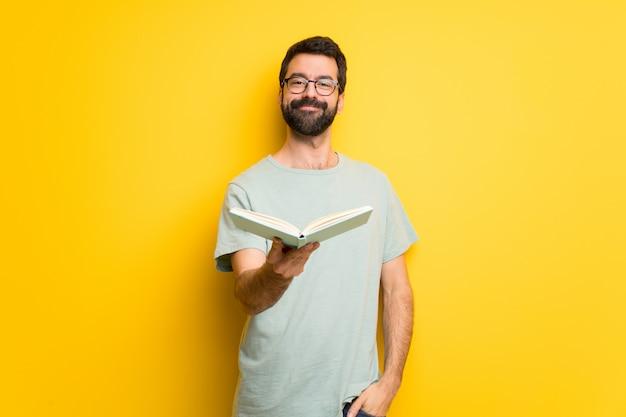 Hombre con barba y camisa verde que sostiene un libro y se lo da a alguien.