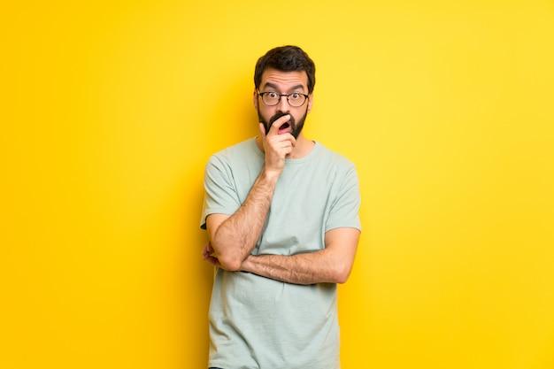 Hombre con barba y camisa verde sorprendido y sorprendido mientras mira a la derecha