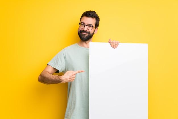Hombre con barba y camisa verde sosteniendo un cartel vacío para insertar un concepto