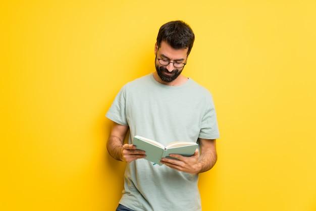Hombre con barba y camisa verde sosteniendo un libro y disfrutando de la lectura
