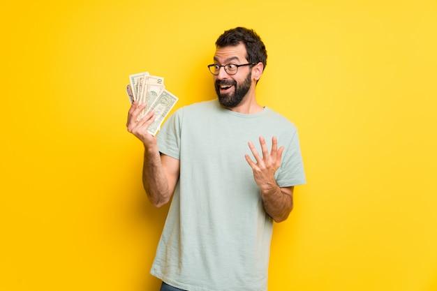 Hombre con barba y camisa verde tomando mucho dinero.