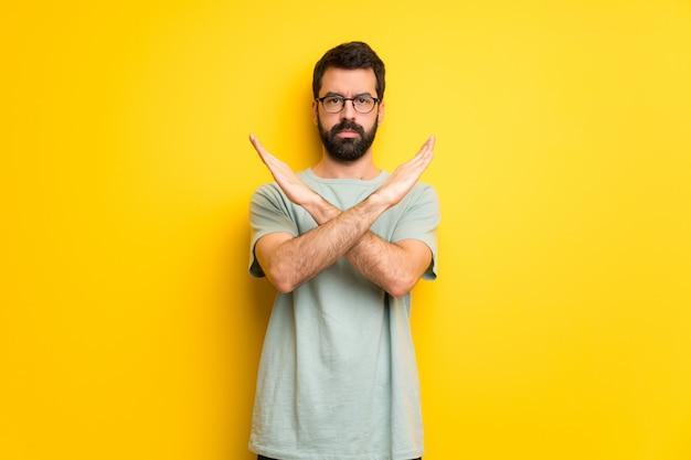 Hombre con barba y camiseta verde sin gesto.