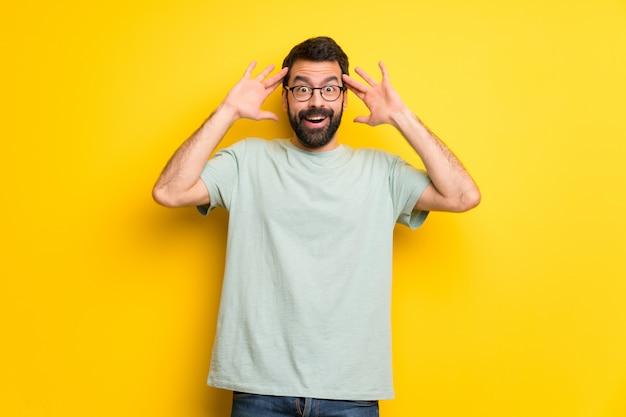 Hombre con barba y camiseta verde con sorpresa y expresión facial conmocionada.