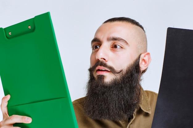 Hombre con barba comprobando dos proyectos diferentes para elegir al ganador.