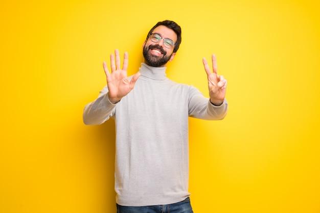 Hombre con barba y cuello alto contando siete con los dedos.
