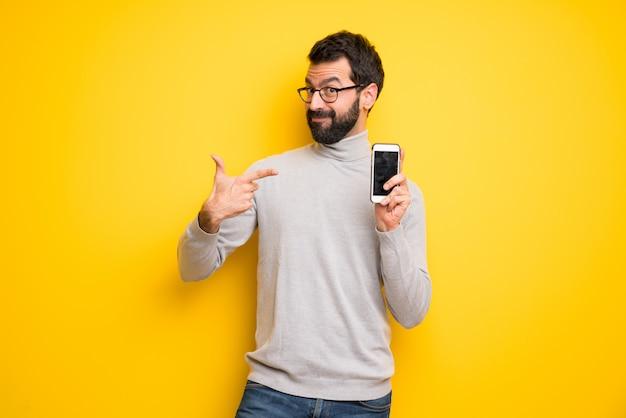 Hombre con barba y cuello alto feliz y apuntando al móvil.