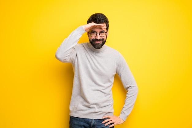 Hombre con barba y cuello alto mirando lejos con la mano para mirar algo